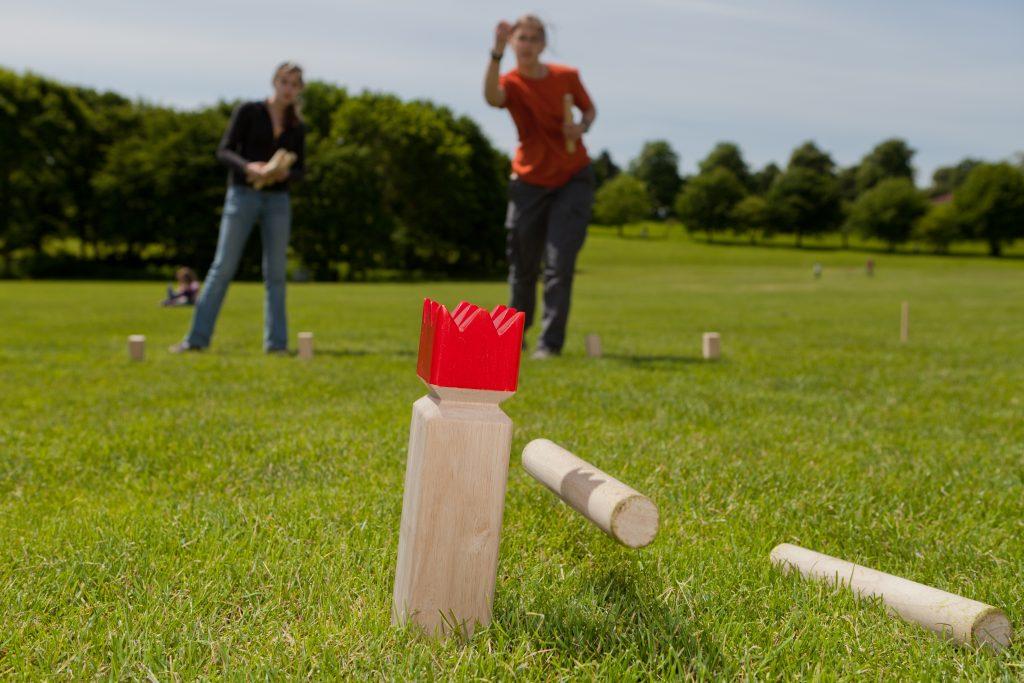 Jugendliche im Park spielen Kubb